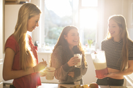 Teenage girls making smoothie in sunny kitchen - HOXF00715