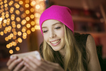 Teenage girl in pink beanie texting with cell phone - HOXF00721