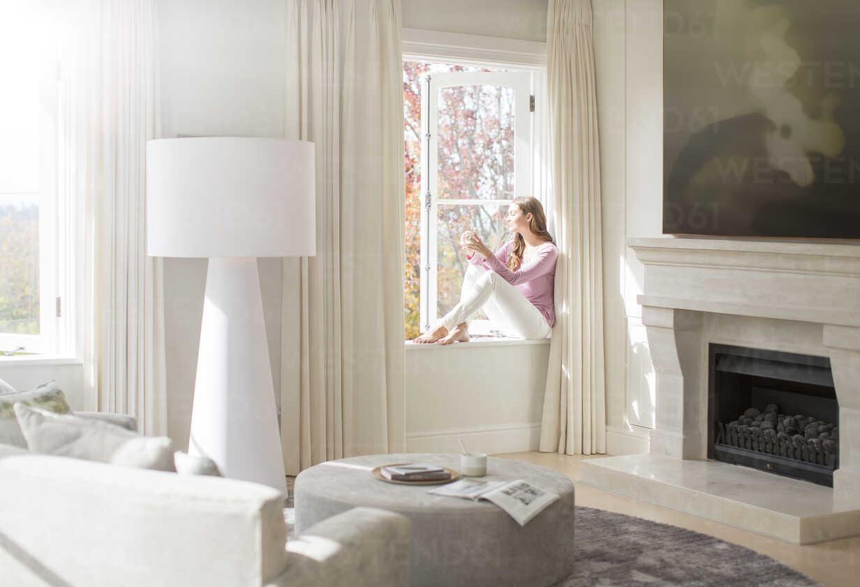 Woman sitting on sunny windowsill - HOXF00733 - Tom Merton/Westend61