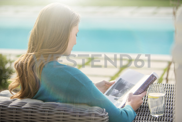 Brunette woman reading magazine at luxury poolside - HOXF00742 - Tom Merton/Westend61