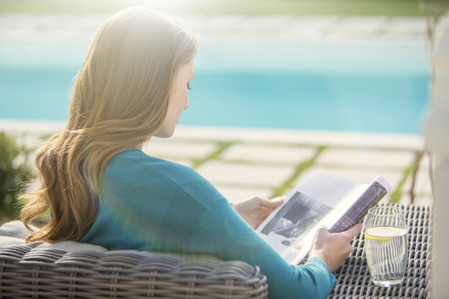 Brunette woman reading magazine at luxury poolside - HOXF00742