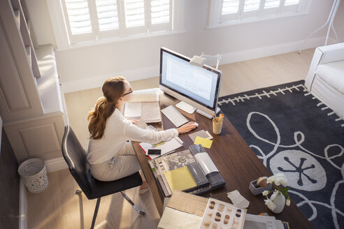 Interior designer working at computer in home office - HOXF00745