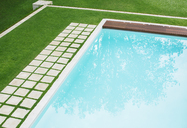 Paving stones in a row along swimming pool in backyard - HOXF00760