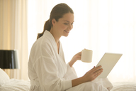 Woman in bathrobe drinking coffee and using digital tablet in bedroom - HOXF00769