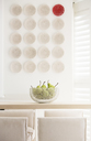 Red plate among white plates on wall in luxury dining room - HOXF00775