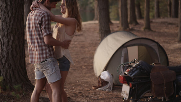 Affectionate young couple hugging outside tent in woods - HOXF00781
