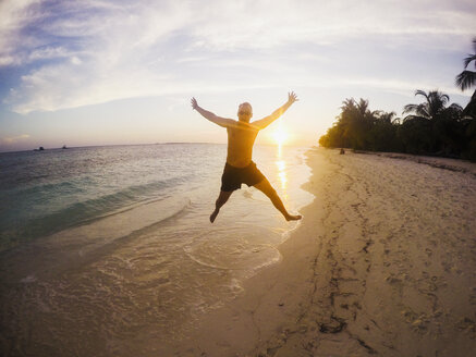 Portrait of exuberant man jumping on tropical beach at sunset - HOXF00793