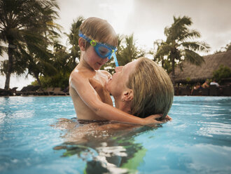 Mother and son hugging in swimming pool - HOXF00796
