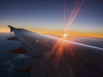 Sunset behind airplane wing in sky - HOXF00814