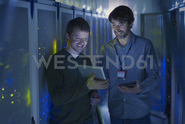 Server room technicians using digital tablet - HOXF00817