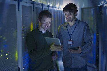 Server room technicians using digital tablet - HOXF00817