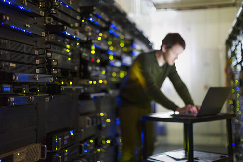 Server room technician working at laptop in corridor - HOXF00865