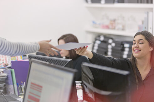 Businesswoman handing paperwork to colleague in office - HOXF00880