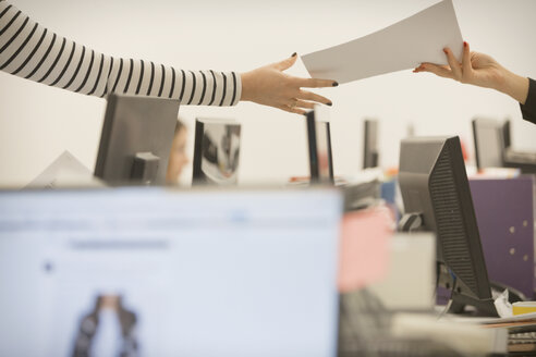 Businesswoman handing paperwork to colleague in office - HOXF00892