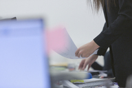 Businesswoman holding paperwork in office - HOXF00934