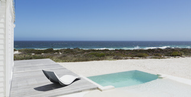 Soaking pool and modern lounge chair with ocean view under sunny blue sky - HOXF00946