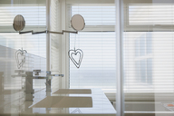 Heart-shape decoration hanging from mirror in modern white home showcase bathroom - HOXF00982