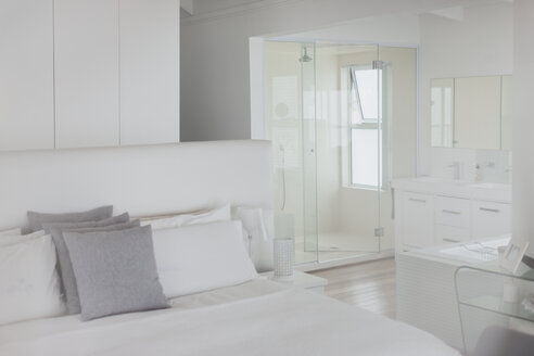 White bedroom and en suite bathroom in home showcase interior - HOXF00988