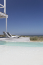 Modern lounge chairs at poolside with ocean view under sunny blue sky - HOXF00991