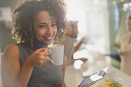 Portrait smiling businesswoman drinking coffee using digital tablet - HOXF00997