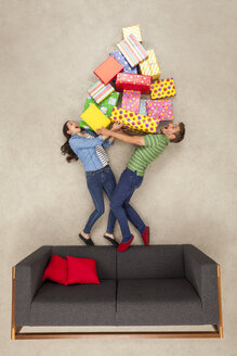 Couple standing on couch, holding big pile of presents - BAEF01574
