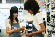 Two smiling women in a store with clipboard - EBSF02200
