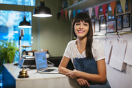 Portrait of happy woman with laptop in a store - EBSF02206