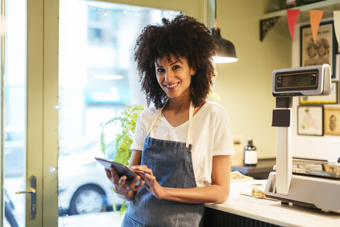 Portrait of smiling woman with tablet in a store - EBSF02218