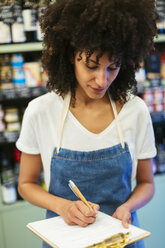 Woman in a store taking notes on clipboard - EBSF02227
