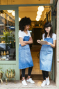 Two smiling women with clipboard standing in entrance door of a store - EBSF02230