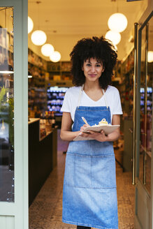 Portrait of smiling woman with clipboard standing in entrance door of a store - EBSF02233