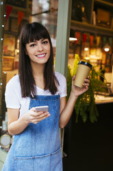 Portrait of smiling woman with cell phone and takeaway coffee in entrance door of a store - EBSF02242