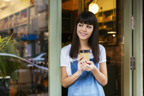 Smiling woman standing at entrance door of a store holding takeaway coffee - EBSF02245