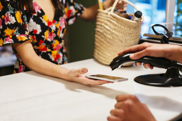 Close-up of customer paying cashless with smartphone at counter of a store - EBSF02260