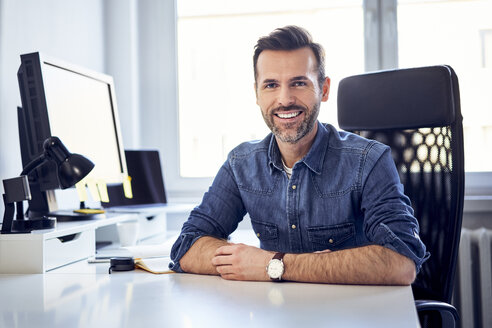 Portrait of smiling man sitting at desk in office - BSZF00239