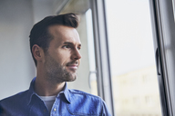 Portrait of confident man looking out of window - BSZF00245