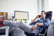 Relaxed man sitting at desk in office talking on cell phone - BSZF00254