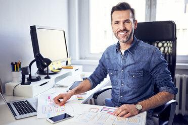 Portrait of smiling web designer working on draft at desk in office - BSZF00263