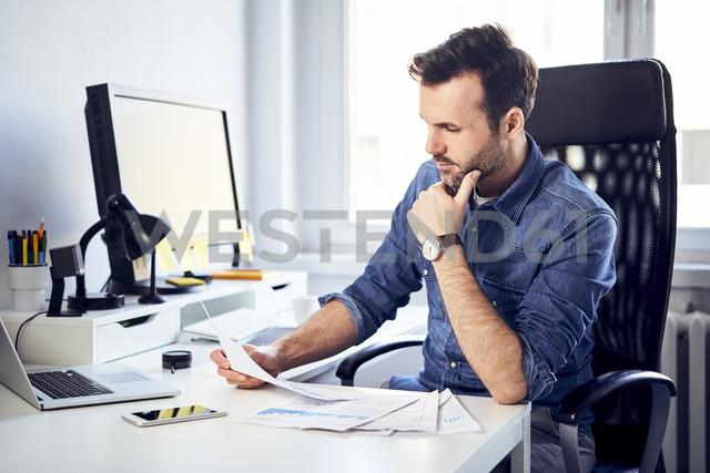 Man reading document at desk in office - BSZF00266 - Bartek Szewczyk/Westend61