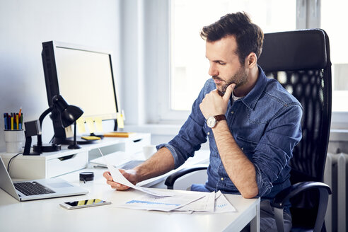 Man reading document at desk in office - BSZF00266