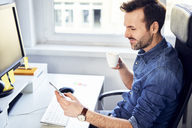 Smiling man looking at cell phone and drinking coffee at desk in office - BSZF00269