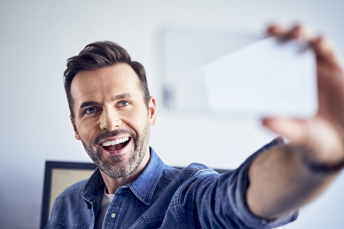 Happy man in office taking selfie - BSZF00275