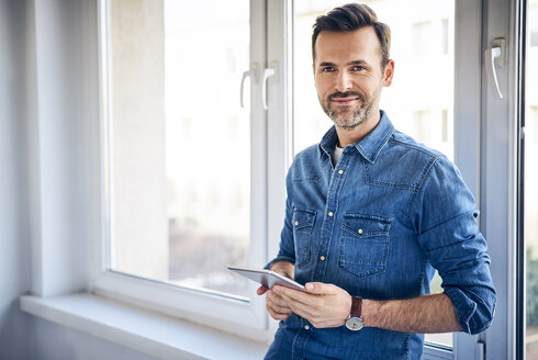 Portrait of smiling man holding tablet at the window - BSZF00278