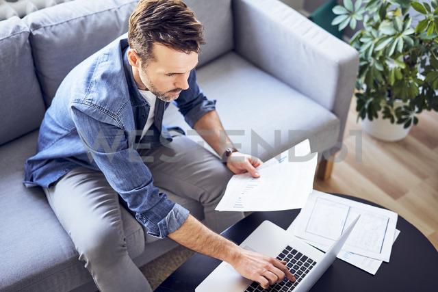 Man with documents sitting on sofa using laptop - BSZF00281 - Bartek Szewczyk/Westend61