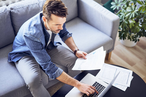 Man with documents sitting on sofa using laptop - BSZF00281
