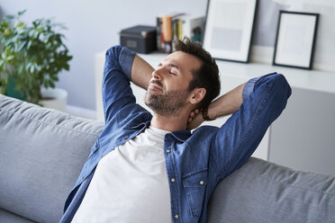 Smiling relaxed man sitting on sofa daydreaming - BSZF00287