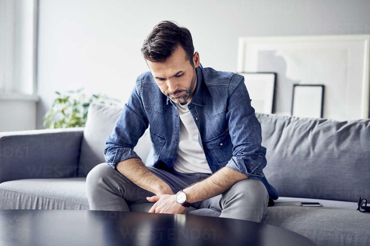 Worried sad man sitting on sofa - BSZF00290 - Bartek Szewczyk/Westend61