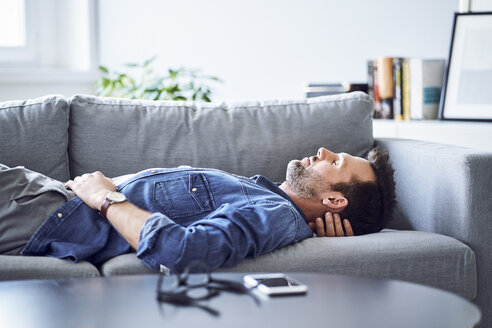 Relaxed man sleeping on sofa - BSZF00296