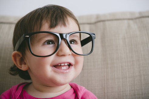 Portrait of laughing baby girl wearing oversized glasses - GEMF01900
