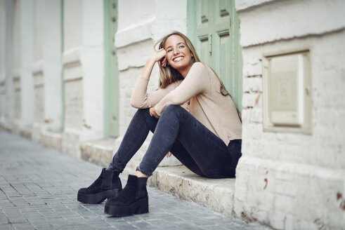 Laughing young woman sitting on step in front of an entrance door - JSMF00041